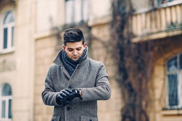 Een knappe jongeman in een warme jas, lederen handschoenen met een horloge tijdens een stadswandeling