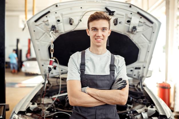 Een knappe jongeman is in een autowerkplaats.