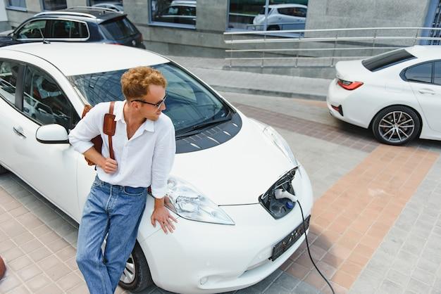 Een knappe jongeman laadt zijn moderne elektrische auto op.