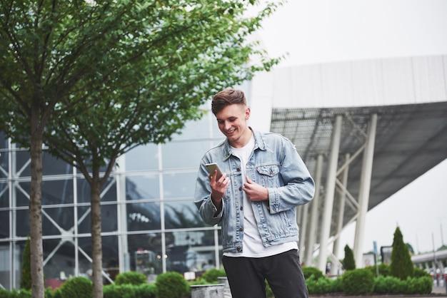 Een knappe jongeman praten aan de telefoon in de buurt van de kantoorruimte.