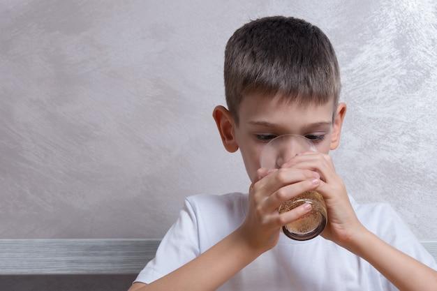 Een knappe jongen drinkt bruisend water uit een glasglas, close-up, exemplaarruimte. ongezond voedselconcept, favoriete voedsel van kinderen