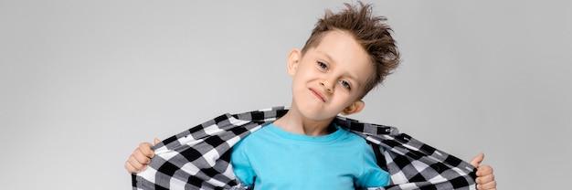 Een knappe jongen in een geruit hemd, blauw shirt en spijkerbroek staat.