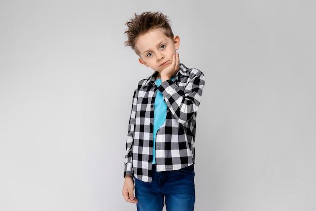 Een knappe jongen in een geruit hemd, een blauw shirt en een spijkerbroek