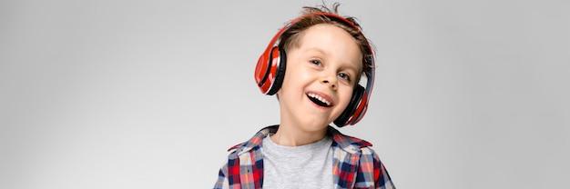 Een knappe jongen in een geruit hemd, grijs shirt en spijkerbroek staat. een jongen in een rode koptelefoon. de jongen houdt zijn handen op zijn buik. de jongen lacht.