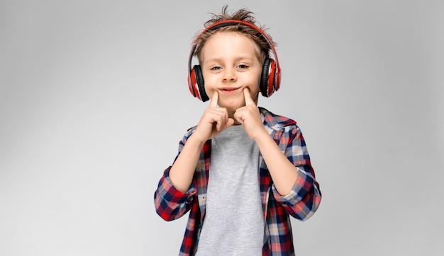 Een knappe jongen in een geruit hemd, grijs shirt en spijkerbroek staat. een jongen in een rode koptelefoon. de jongen strekt zijn vingers uit met een glimlach.