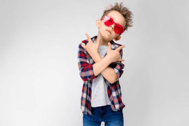 Een knappe jongen in een geruit hemd, grijs shirt en spijkerbroek staat. een jongen in rode zonnebril. de jongen toont een rocker geit.