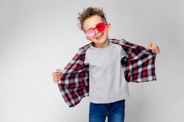 Een knappe jongen in een geruit hemd, grijs shirt en spijkerbroek staat grijs. een jongen in rode zonnebril. de jongen trekt zijn shirt naar achteren.