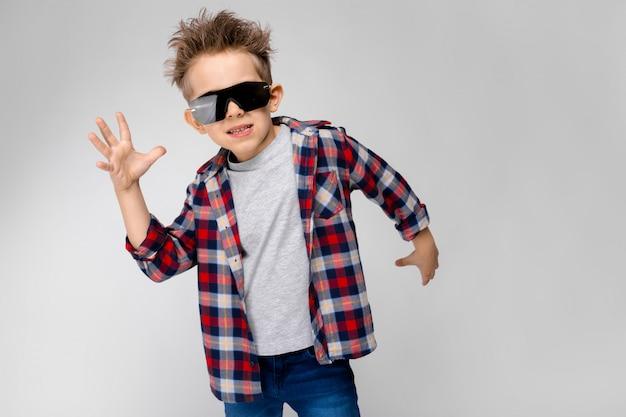 Een knappe jongen in een geruit hemd, grijs shirt en spijkerbroek staat op grijs