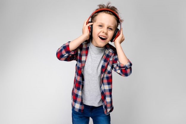 Een knappe jongen in een plaid shirt, grijs shirt en spijkerbroek staat op een grijze achtergrond. een jongen in rode koptelefoon zingt een lied.