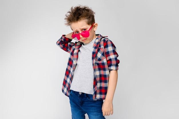 Een knappe jongen in een plaid shirt, grijs shirt en spijkerbroek staat op een grijze achtergrond. een jongen in rode zonnebril.