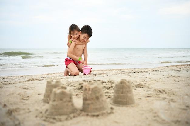 Een knappe jongen vult een speelgoedemmer met zeezand en lacht liefjes en zijn jongere zus knuffelt zachtjes