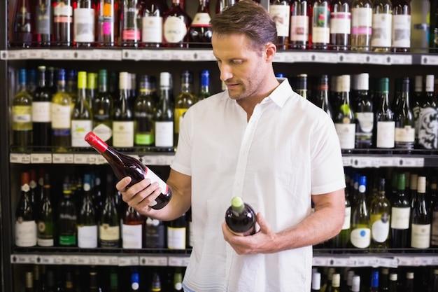 Een knappe kijkend naar wijnfles in supermarkt