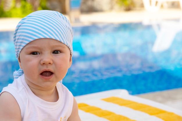 Een knappe, kleine jongen zit op een ligstoel bij het zwembad. selectieve aandacht.
