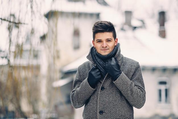 Een knappe lachende jonge man in een warme jas en lederen handschoenen tijdens het wandelen in de stad