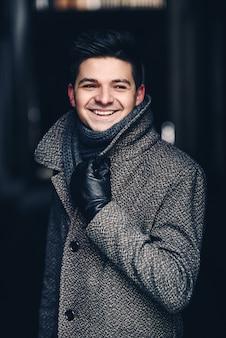 Een knappe lachende jonge man in warme jas en lederen handschoenen