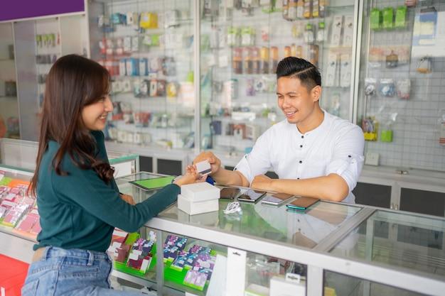 Een knappe man bedient een vrouwelijke klant door te betalen met een creditcard Premium Foto