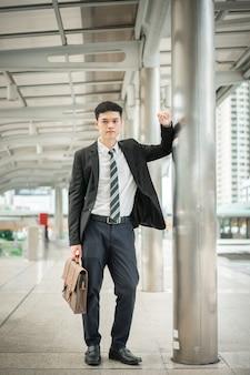 Een knappe man die een zwart pak en een wit shirt draagt, houdt een handtas vast en staat in de stad.