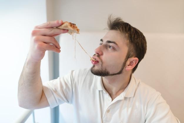Een knappe man eet een heet stuk pizza. de man eet een kaas die zich uitstrekt met een stuk pizza.
