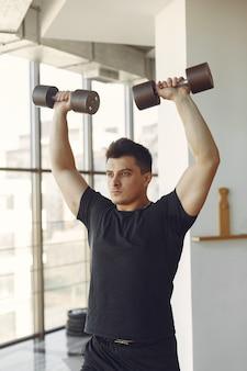Een knappe man houdt zich bezig met een sportschool