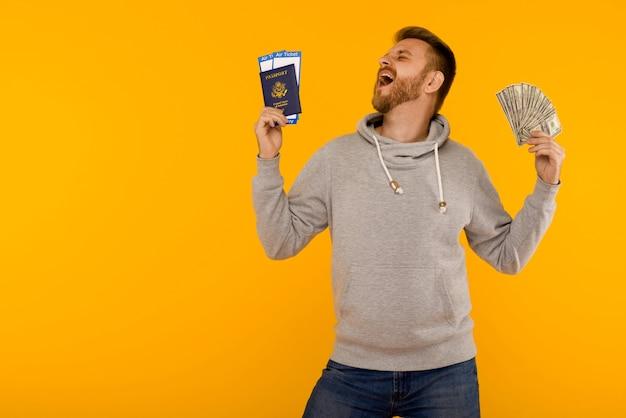 Een knappe man in een grijze hoodie verheugt zich over het winnen van de loterij. hij houdt een paspoort met vliegtickets en geld dollars op een gele achtergrond.