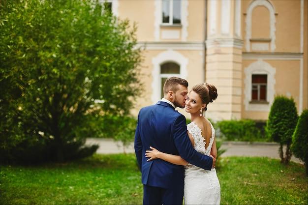 Een knappe man in een trendy blauw pak knuffelt en kust een mooie modelvrouw in een trouwjurk