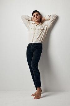 Een knappe man in een wit overhemd en een zwarte broek leunde met zijn armen tegen de muur. hoge kwaliteit foto