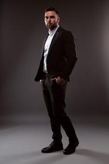 Een knappe man in een zwart pak en een wit overhemd