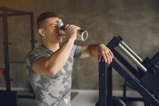 Een knappe man is bezig met een sportschool