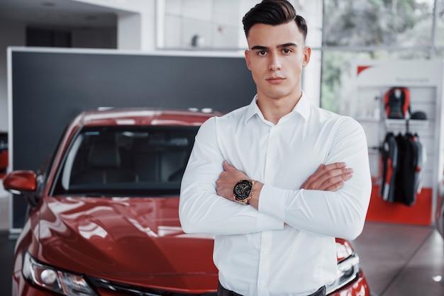 Een knappe man is een koper die naast een nieuwe auto bij het dealercentrum naar de camera kijkt.