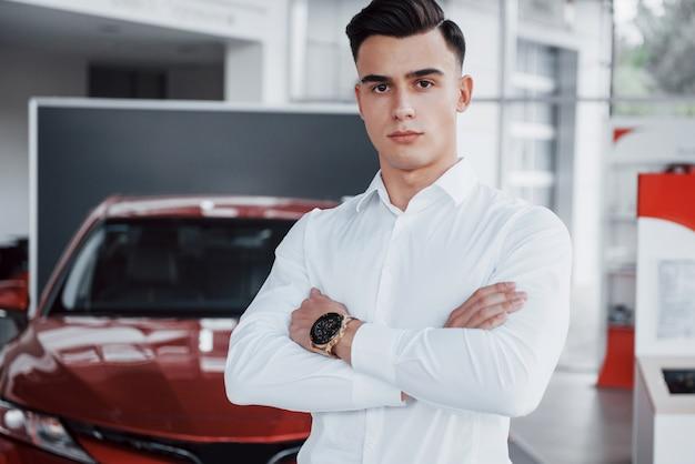 Een knappe man is een koper die naast een nieuwe auto in het dealercentrum staat en naar de camera kijkt.