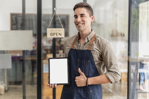 Een knappe man is in een café, hij staat met een mockup-tablet voor een welkomstbericht of een menu, hij is een cafémedewerker die een schort draagt en klanten bedient. café dienstverleningsconcept.