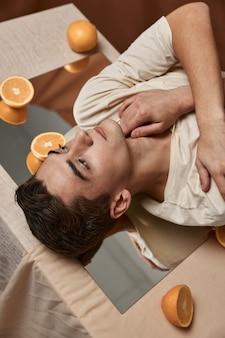 Een knappe man ligt op de tafel spiegel sinaasappels close-up studio. hoge kwaliteit foto