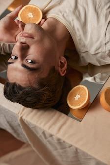 Een knappe man ligt op een tafel op een spiegel met sinaasappels. hoge kwaliteit foto