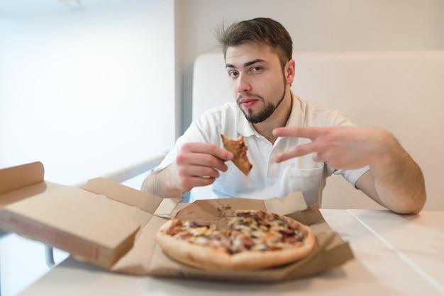 Een knappe man met een stuk pizza in zijn handen vormt op de camera. man zit aan een tafel in de buurt van de pizzadoos
