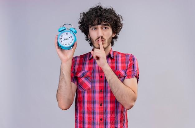 Een knappe man met krullend haar in geruit overhemd die wijsvinger op mond houdt met blauwe wekker