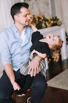 Een knappe man speelt thuis met zijn grappige dochter bij de kerstboom