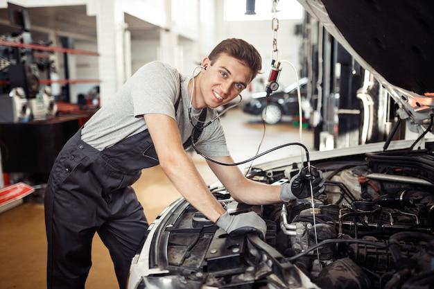 Een knappe monteur lacht terwijl hij een motor controleert.
