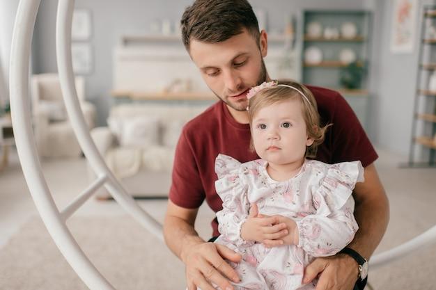 Een knappe sterke man in een lichte kamer met zijn schattige dochtertje zit op een ronde schommel