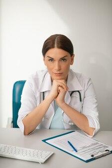 Een knappe vrouwelijke arts in een wit gewaad die er attent uitziet