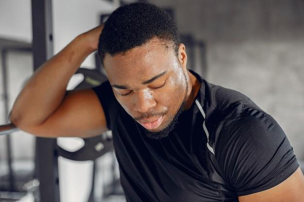 Een knappe zwarte man is bezig met een sportschool