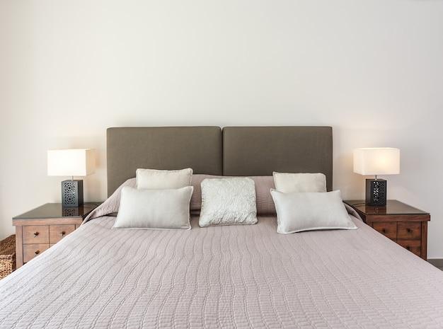 Een knus bed voor twee in de slaapkamer. armaturen zijn verlicht.