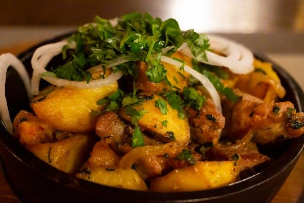 Een koekenpan met aardappelvlees en gebakken uien op een houten tafel het concept van kaukasisch en rusland...