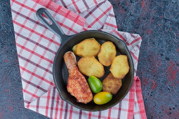 Een koekenpan met kippenvlees en groenten.