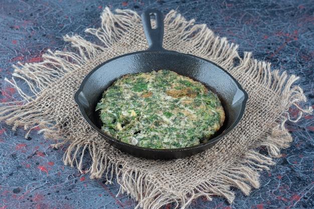 Een koekenpan omelet met groenten.