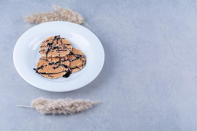 Een koekenpan van ronde rossige wafel met hagelslag en room.