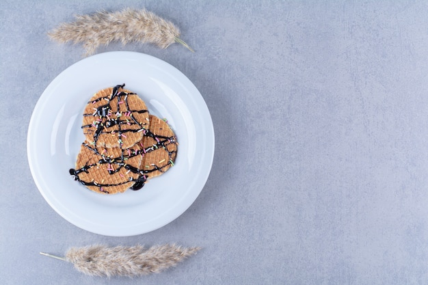 Een koekenpan van ronde rossige wafel met hagelslag en room