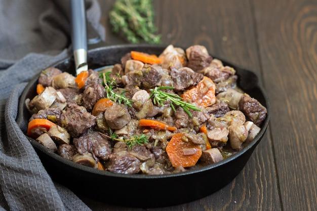 Een koekepan met rundvlees bourguignon met worstjes, wortelen, knoflook, ui, rode wijn, kruiden en specerijen.