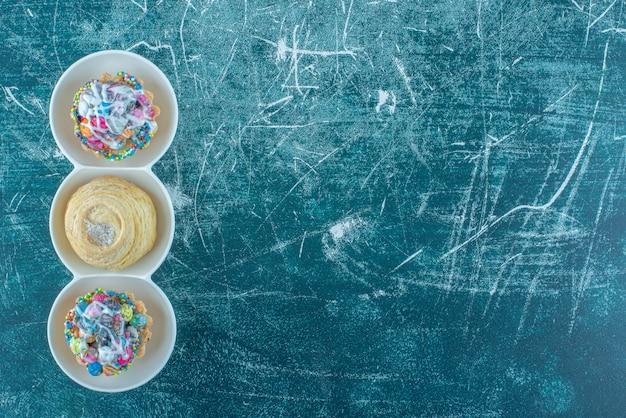 Een koekje en cupcakes in een kleine serveerschaal op blauwe achtergrond. hoge kwaliteit foto