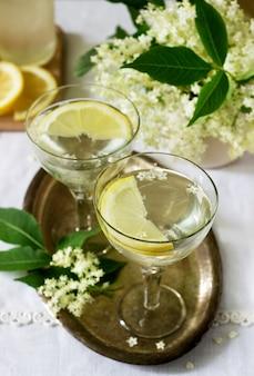 Een koel drankje met citroen en vlierbloesemsiroop in glazen op een metalen dienblad. rustieke stijl.