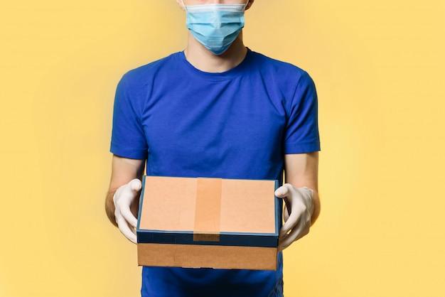 Een koerier in een medisch masker en beschermende handschoenen houdt een pakket, staande geïsoleerd op een gele muur met plaats voor tekst.